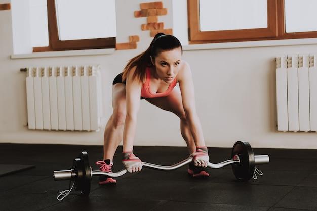 Caucasian sportswoman is exercising in gym alone Premium Photo