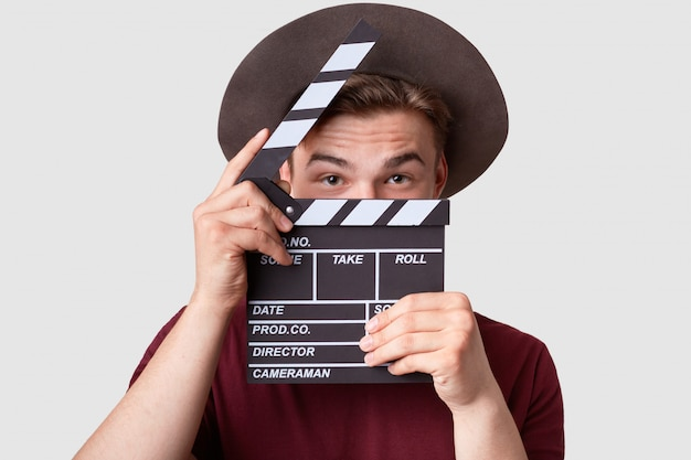 Caucasian successful male producer looks through opened clapperboard Free Photo
