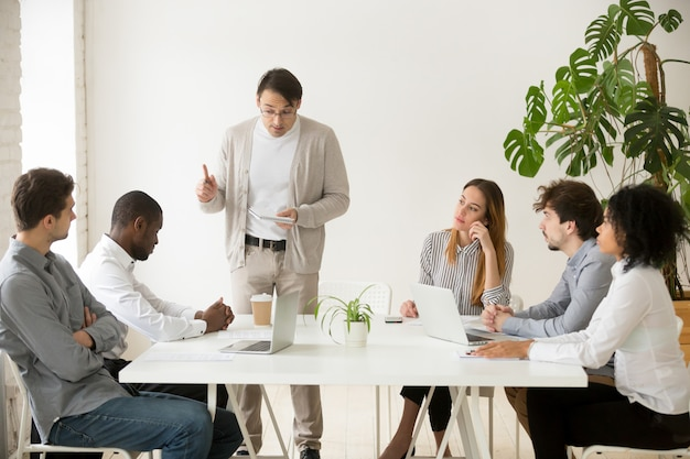 Caucasian team leader rebuking african employee for mistake at meeting Free Photo