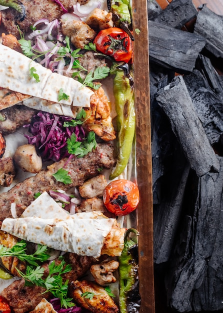 Caucasian traditional kebab platter with grilled foods and herbs. Free Photo