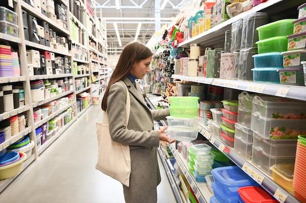 Кавказская женщина выбирает контейнер для еды в супермаркете. Premium Фотографии