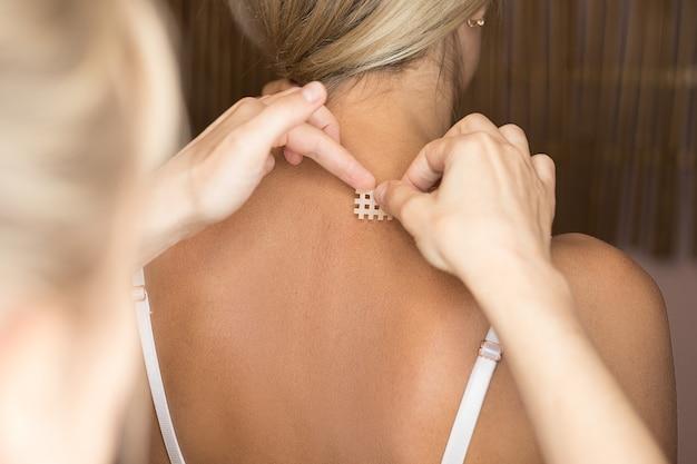 Кавказской женщине наложили поперечную кинезиотейп на шею для снятия боли при шейном синдроме Premium Фотографии
