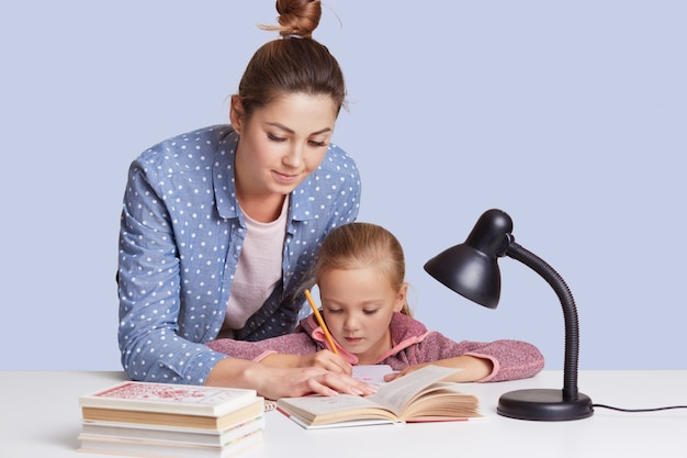 Caucasian woman helping her doughter to do school homework, mother and child surronded by books, little girl sitting concentrated at white desk, trying to do sums. education concept. Free Photo