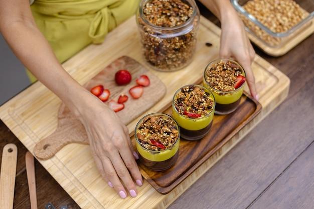 キッチンの白人女性がマンゴージャムでチアプリンを作っています。アーモンドミルク、チアシード、ココア、マンゴージャム、グラノーラでできたデザート。 無料写真
