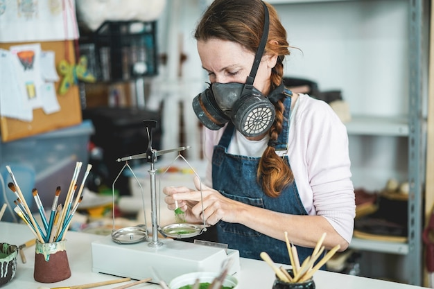 Caucasian woman mixing painting colors with a vintage balance inside her creative pottery studio - focus on her eye Premium Photo