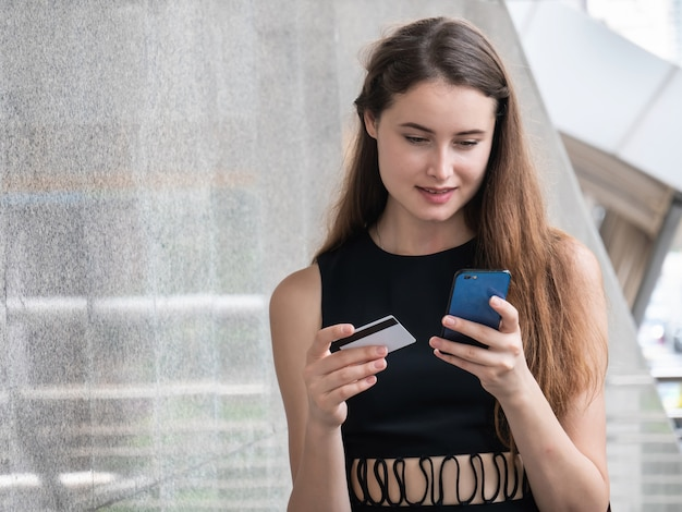 Caucasian woman paying online with credit card and smart phone outdoors in the city Premium Photo