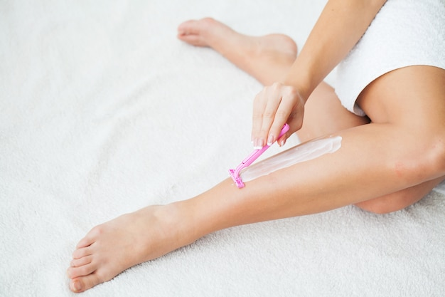 Caucasian woman shaving legs with razor at home Premium Photo