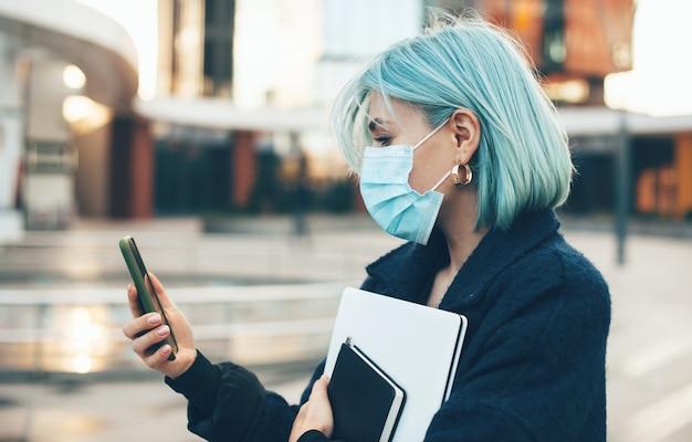 Кавказская женщина с синими волосами болтает с кем-то в защитной маске и держит компьютер на улице Premium Фотографии