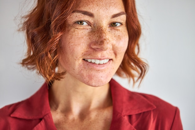 Caucasian woman with red hair and green eyes posing, smiling at camera isolated in studio background, people and lifestyle concept Premium Photo
