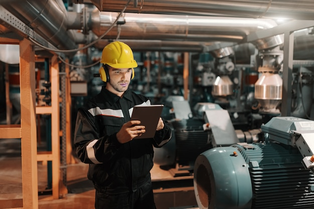 Caucasian worker in heavy industry plant with helmet and in uniform using tablet for work. Premium Photo