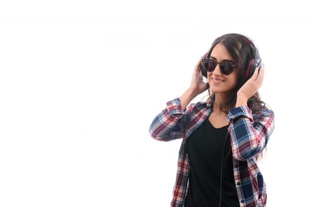 白い背景に分離された大きなヘッドフォンで音楽を聴く白人少女 Premium写真