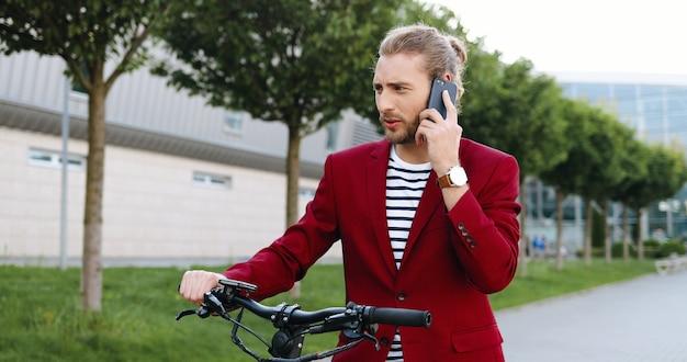Кавказский молодой красавец в красной куртке, стоя на улице на велосипеде или электрическом скутере и разговаривая по мобильному телефону. стильный парень разговаривает по мобильному телефону на открытом воздухе. велосипед. велосипедист разговаривает по телефону. Premium Фотографии