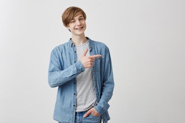 Кавказский молодой мужчина усмехается, указывает на копию пространства, рекламирует что-то. счастливый человек указывает на переднего пальца, доволен выражением, улыбается с брекетами смотри сюда! Бесплатные Фотографии