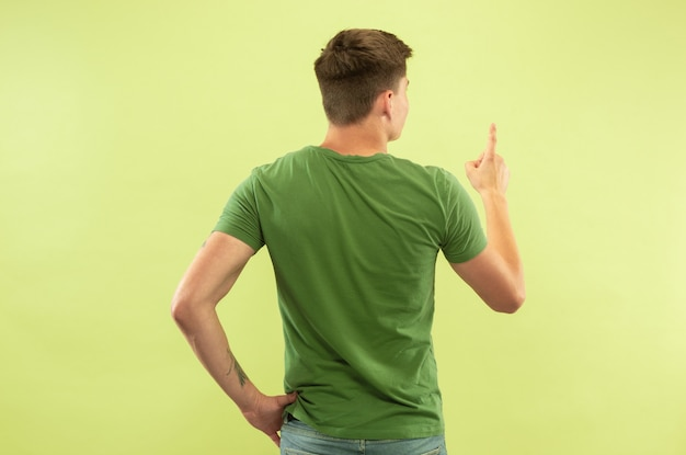Ritratto a mezzo busto del giovane caucasico su sfondo verde studio. bellissimo modello maschile in camicia. concetto di emozioni umane, espressione facciale, vendite, annuncio. mostrare e indicare qualcosa. Foto Gratuite