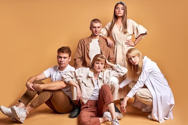 白人の若者は、同じスタイリッシュな服を着て、茶色で隔離された床に一緒に座っています Premium写真