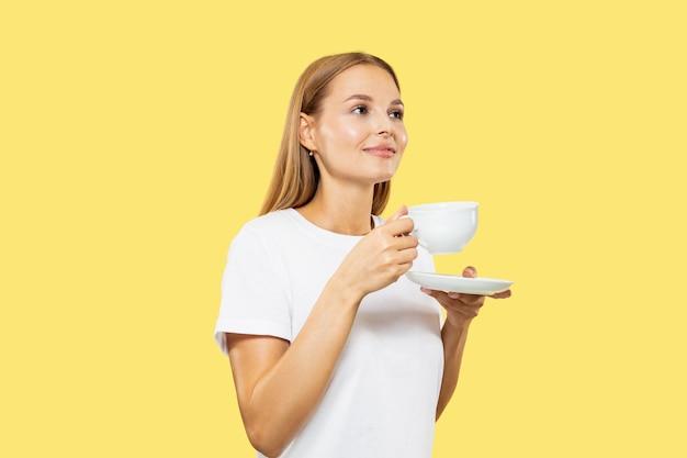 Поясной портрет кавказской молодой женщины на желтом фоне студии. красивая женская модель в белой рубашке. концепция человеческих эмоций, выражения лица, продаж. пить кофе или чай с чашкой. Бесплатные Фотографии