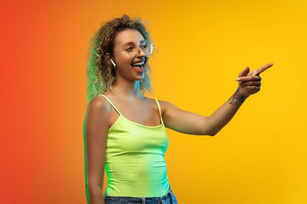ネオンのグラデーションスタジオの背景に分離された白人の若い女性の肖像画。カジュアルなスタイルで美しい女性のカーリーモデル。 無料写真