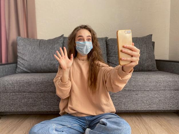 コロナウイルスのパンデミック中に自宅で自己分離で座っている医療マスクを着ている白人の若い女性。 Premium写真