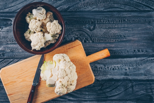 Cauliflower in a bowl and cutting board with knife top view on a dark wooden background Free Photo