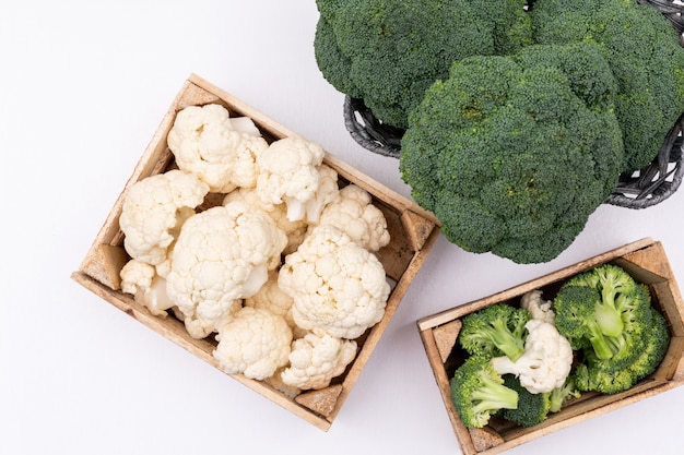Cauliflower in box near the broccoli in basket top view on white surface Free Photo