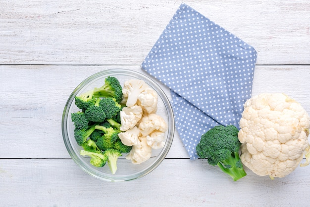 Cauliflower and broccoli in a transparent bowl on a white wooden background. background menu food Premium Photo