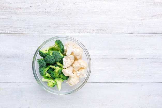 Cauliflower and broccoli in a transparent bowl on a white wooden. Premium Photo