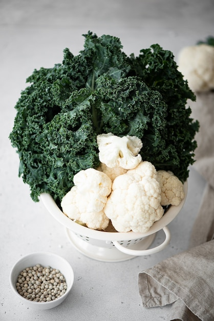 Cauliflower and kale in a white colander on a white table Premium Photo