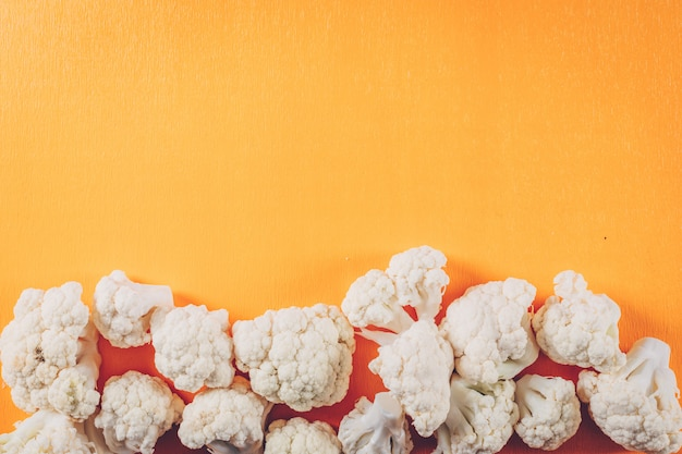 Cauliflower on a orange background. top view. space for text Free Photo