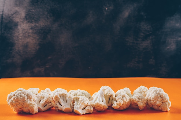 Cauliflower on a orange and dark background. side view. space for text Free Photo