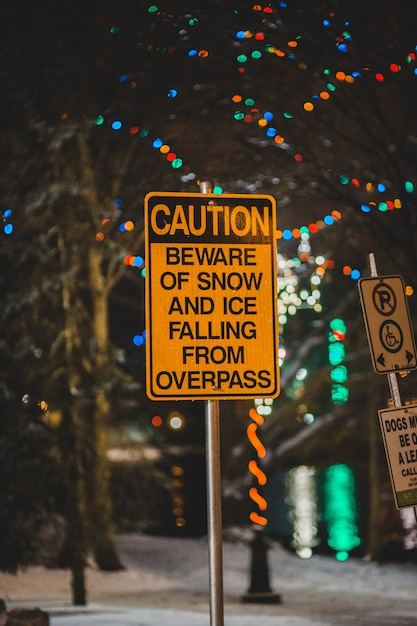 Caution beware of snow and ice falling from overpass sign Free Photo