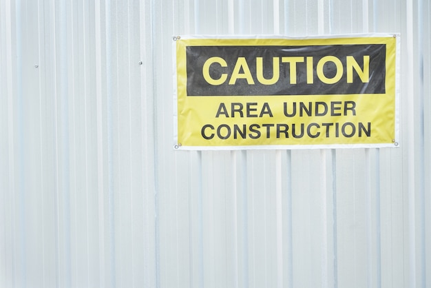 Caution construction area sign on the metal wall Premium Photo