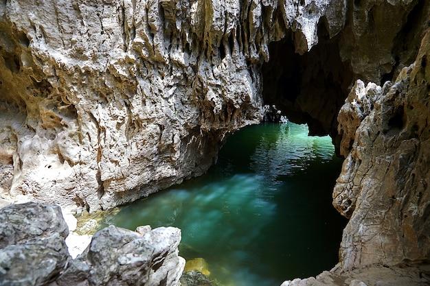 Пещера в скале, наполненная речной водой. блики на каменной поверхности грота. отражение жидкости на стене грота Premium Фотографии
