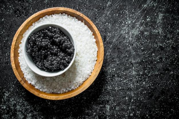 ボウルにキャビアと塩。黒の素朴なテーブルの上 Premium写真