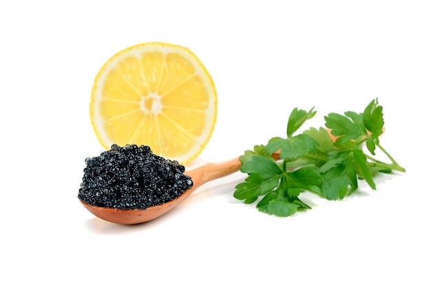 Caviar black in a wooden spoon Premium Photo