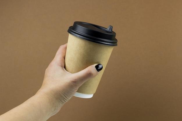 Женская рука держит ccoffee бумажный стаканчик на коричневом фоне Premium Фотографии