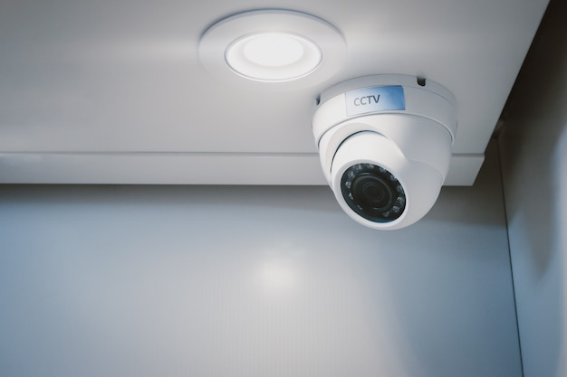 Cctv security camera on wall in the home office for surveillance monitoring home guard system. Premium Photo