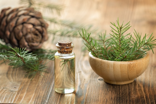 Cedar essential oil in a glass bottle. soft focus. wooden background. Premium Photo