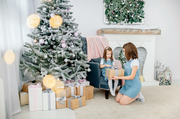 Celebrate christmas, emotions, feelings, precious moments. mom and daughter are laying out a welcome gift near the new year tree Premium Photo