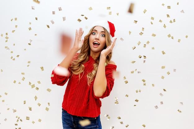 Celebrando la ragazza in cappello di travestimento di babbo natale divertendosi in coriandoli. nuovo umore da festa per le orecchie. accogliente pullover rosso Foto Gratuite