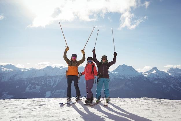 Празднование лыжников, стоящих на заснеженной горе Бесплатные Фотографии