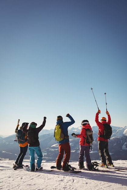 Celebrating skiers standing on snow covered mountain Free Photo