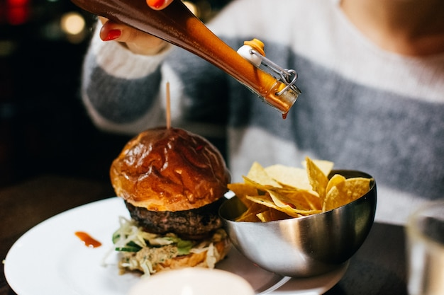 Celebrating with a juicy beef burger in a restaurant Free Photo