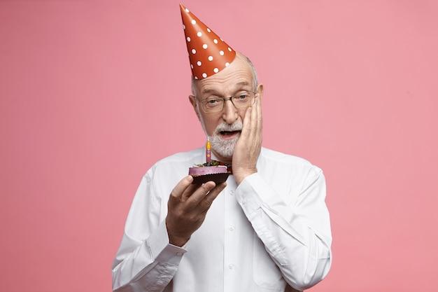 Концепция празднования и годовщины. эмоциональный пожилой мужчина с густой седой бородой, одетый в причудливую элегантную одежду, с праздничным тортом и трогательным лицом в шоке, ошеломленный вечеринкой-сюрпризом Бесплатные Фотографии