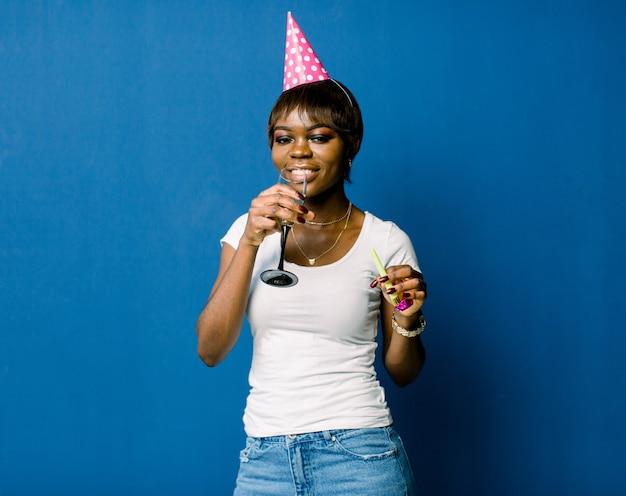 축하와 파티. 재밌어요 흰색 Tshirt와 청바지와 생일 모자에 젊은 꽤 아프리카 여자 웃 고있다. 푸른 공간으로 화려한 스튜디오 초상화입니다. 프리미엄 사진