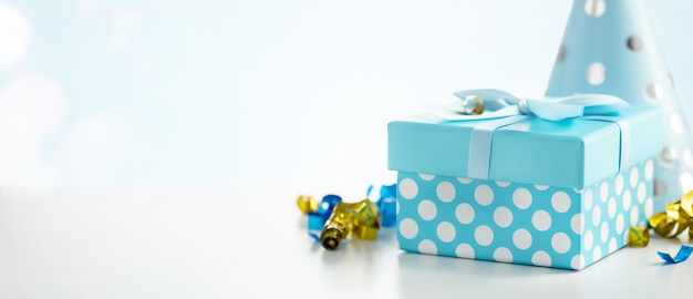 Celebration background with gift box, colorful party streamers, confetti and birthday party hats Premium Photo