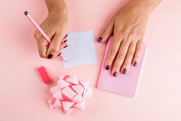 Концепция празднования с луком, мини-ноутбук, ластик на розовом столе плоской планировки. женщина, писать на заметку. Бесплатные Фотографии