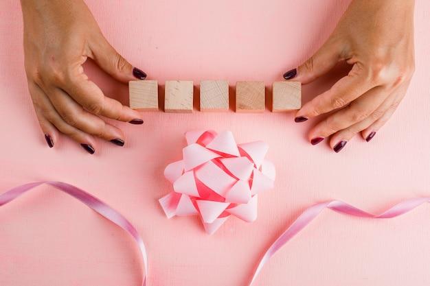 Концепция празднования с бантом, лентой на розовом столе лежал. женщина, держащая деревянные кубики. Бесплатные Фотографии
