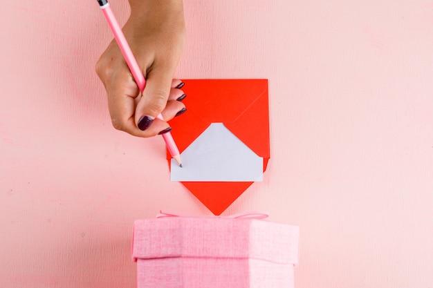 Концепция празднования с подарочной коробке на плоской розовой таблицы лежал. женщина, подписывающая поздравительную открытку. Бесплатные Фотографии