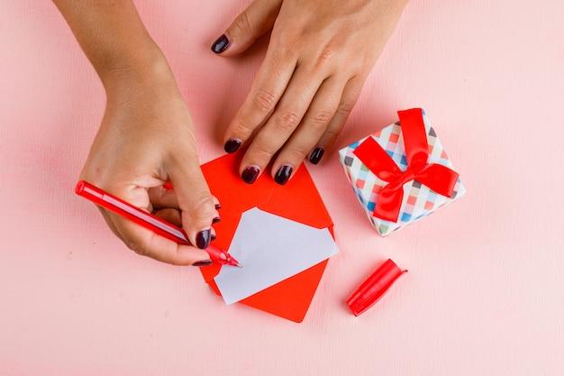 Concetto di celebrazione con il contenitore di regalo sulla disposizione rosa del piano della tavola. biglietto di auguri firma donna. Foto Gratuite