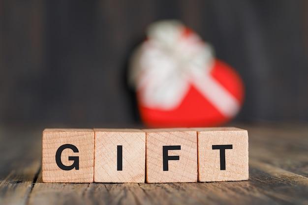 Концепция празднования с подарочной коробке, деревянные кубики на деревянный стол, вид сбоку. Бесплатные Фотографии